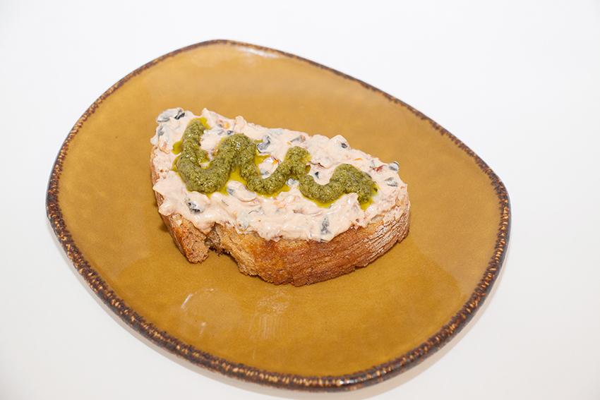 Tosta de paté de queso cremoso con tomates secos, aceitunas y salsa pesto
